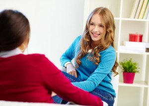 Portrait of happy girl looking at her friend with smile during conversation